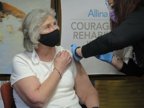 A woman wearing a face mask receives a vaccine shot.