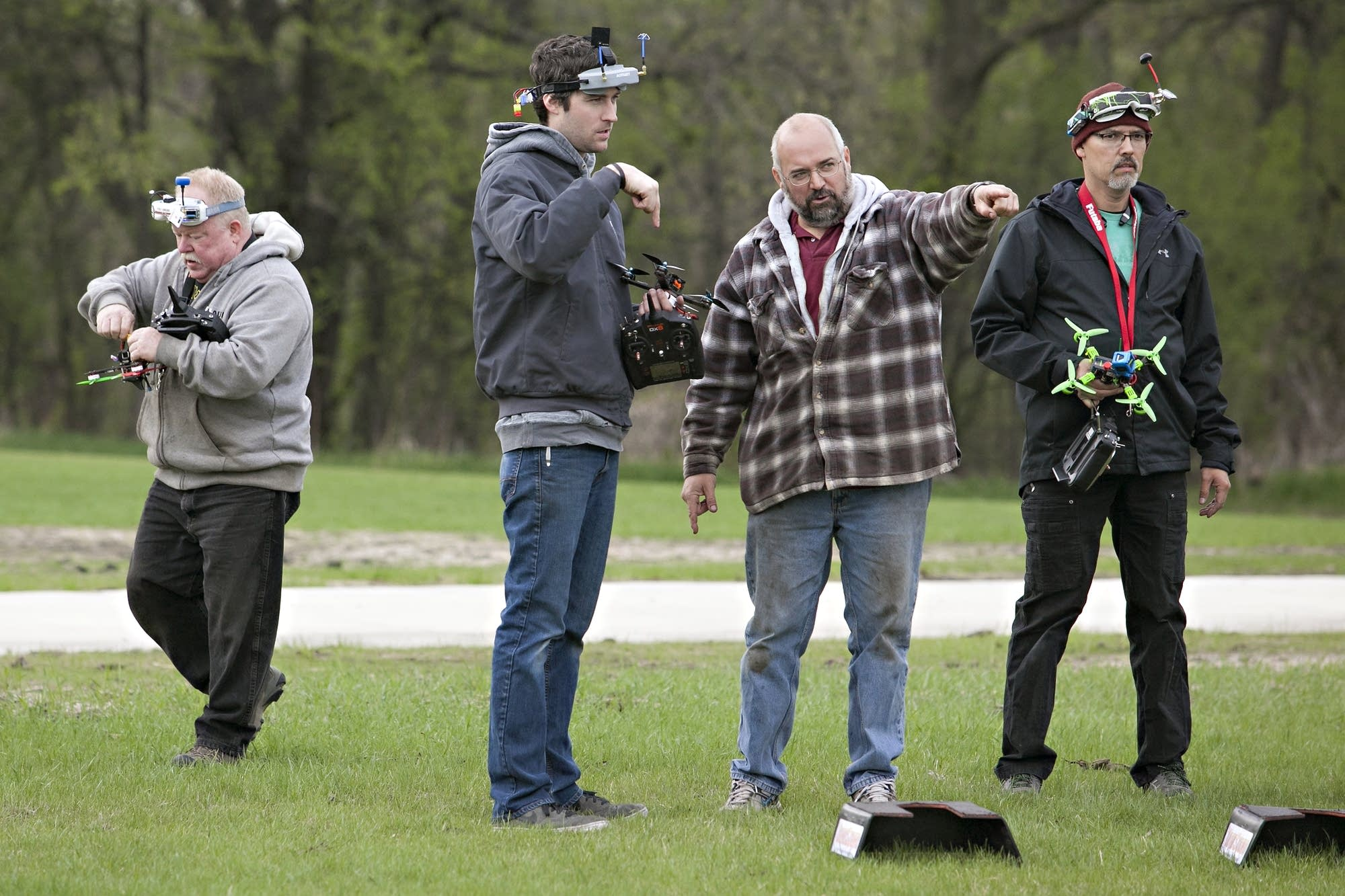 Pilots talk through the drone race course at a park in Moorhead.