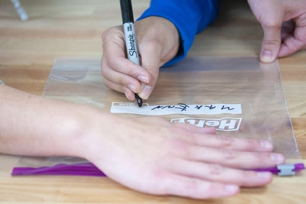 "A teen uses a marker to write ""Makenna"" on a ziplock bag."