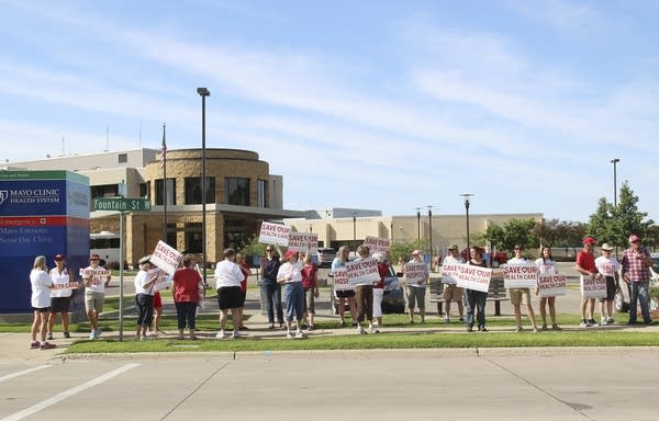 People stand in front of a hospital while holding signs.