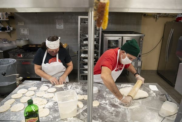 Two people make bread in a commercial kitchen.