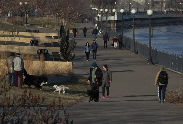 People walking outside near a river