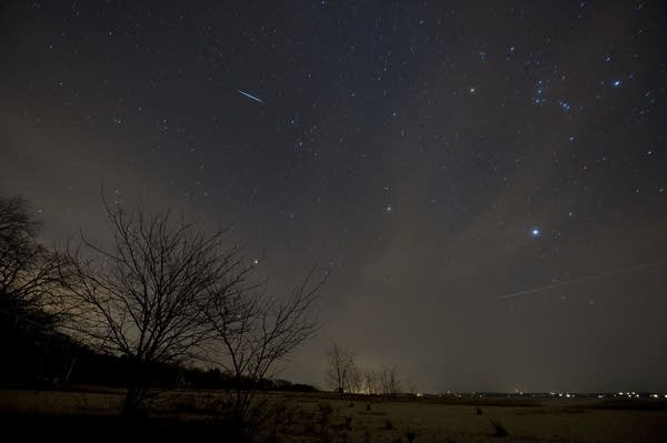 A meteor passes through a night sky.