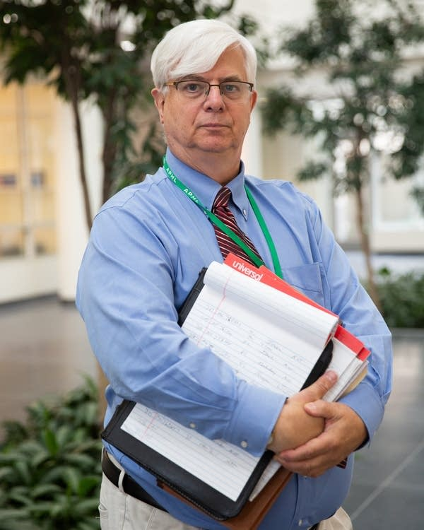 A man holds legal pads.