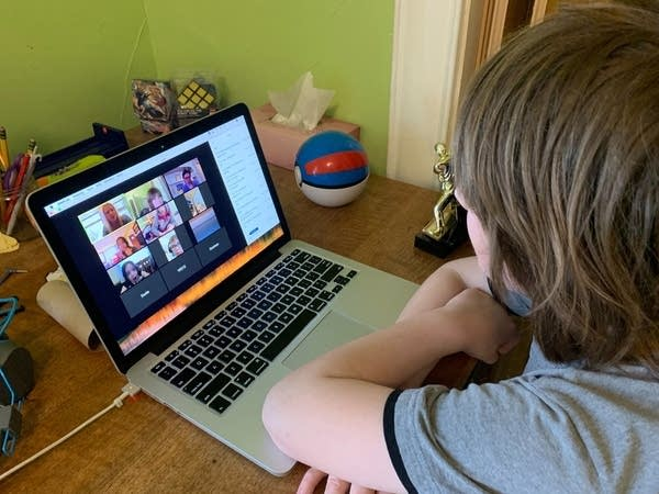 Boy sitting at desk in front of laptop with faces on it.