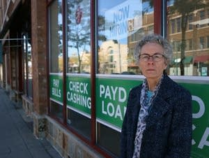 Sara Nelson-Pallmeyer stands for a portrait by a payday lender