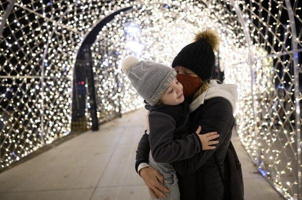 A woman kisses a child.