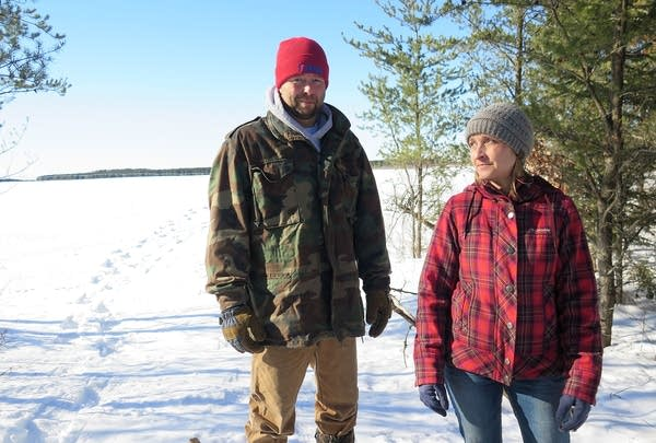 Two people stand near trees in a snow-covered field.