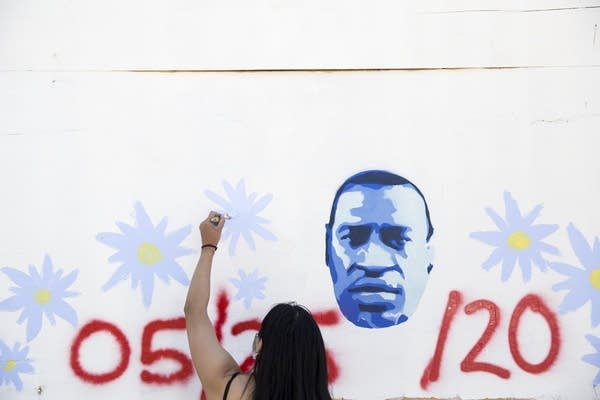 Young person paints a mural on a brick wall.