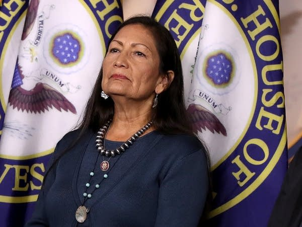 Rep. Deb Haaland stands in front of House flags on a stage.