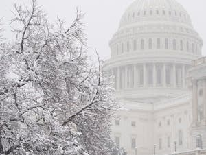 Snow falls at the U.S. Capitol.