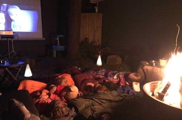 Kids in sleeping bags watching a movie.