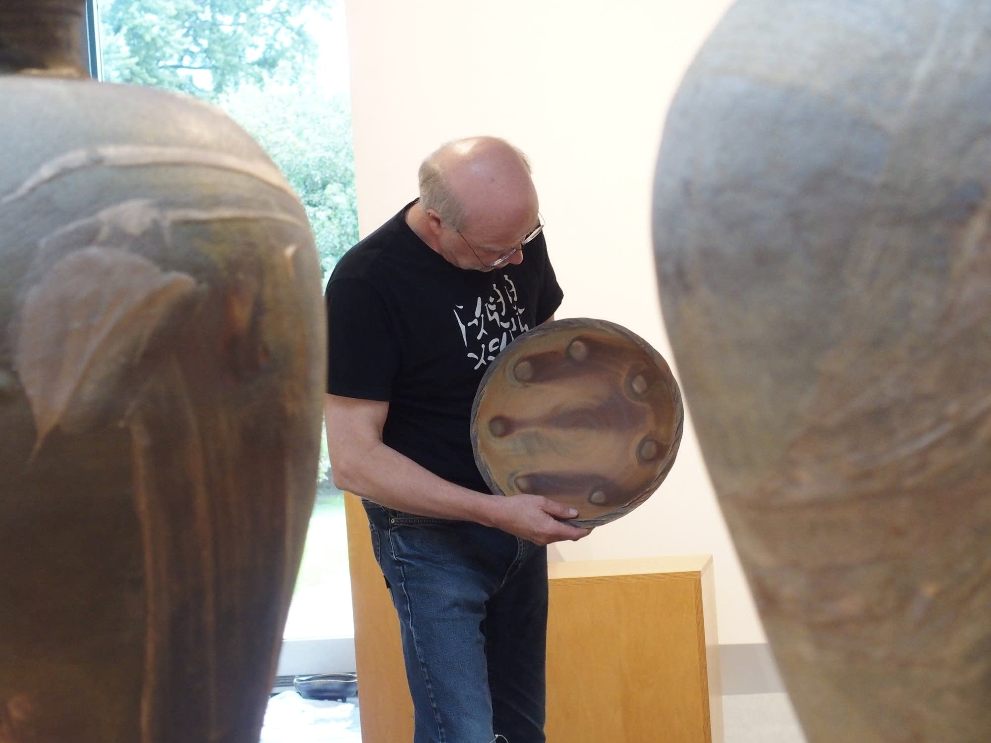Richard Bresnahan examines the pattern on a bowl