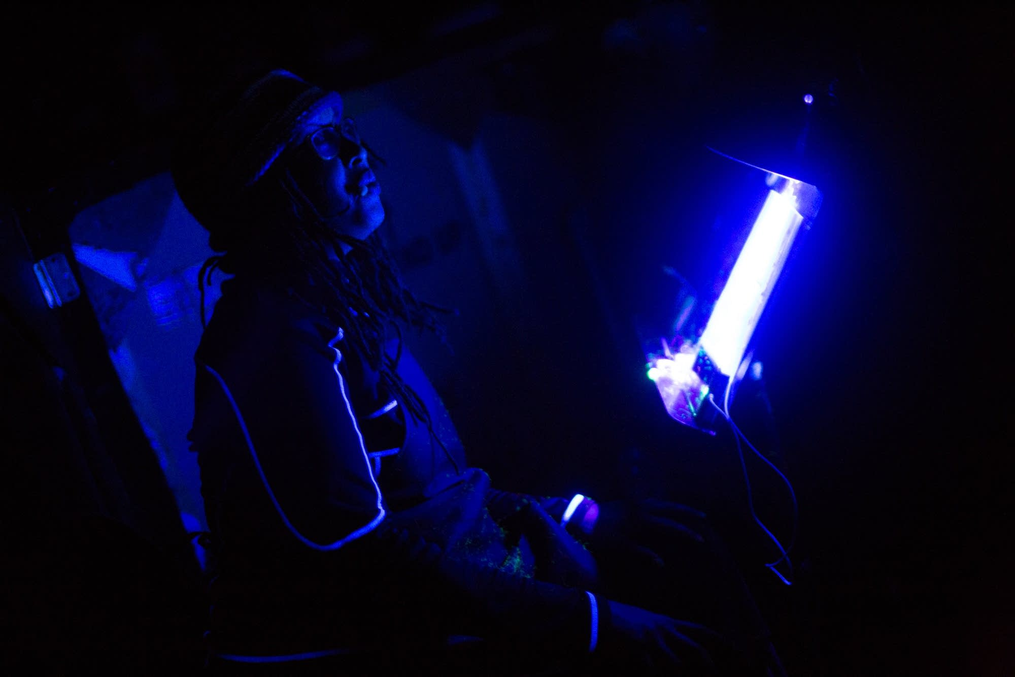 Mankwe Ndosi reads off a script lit by blacklight.