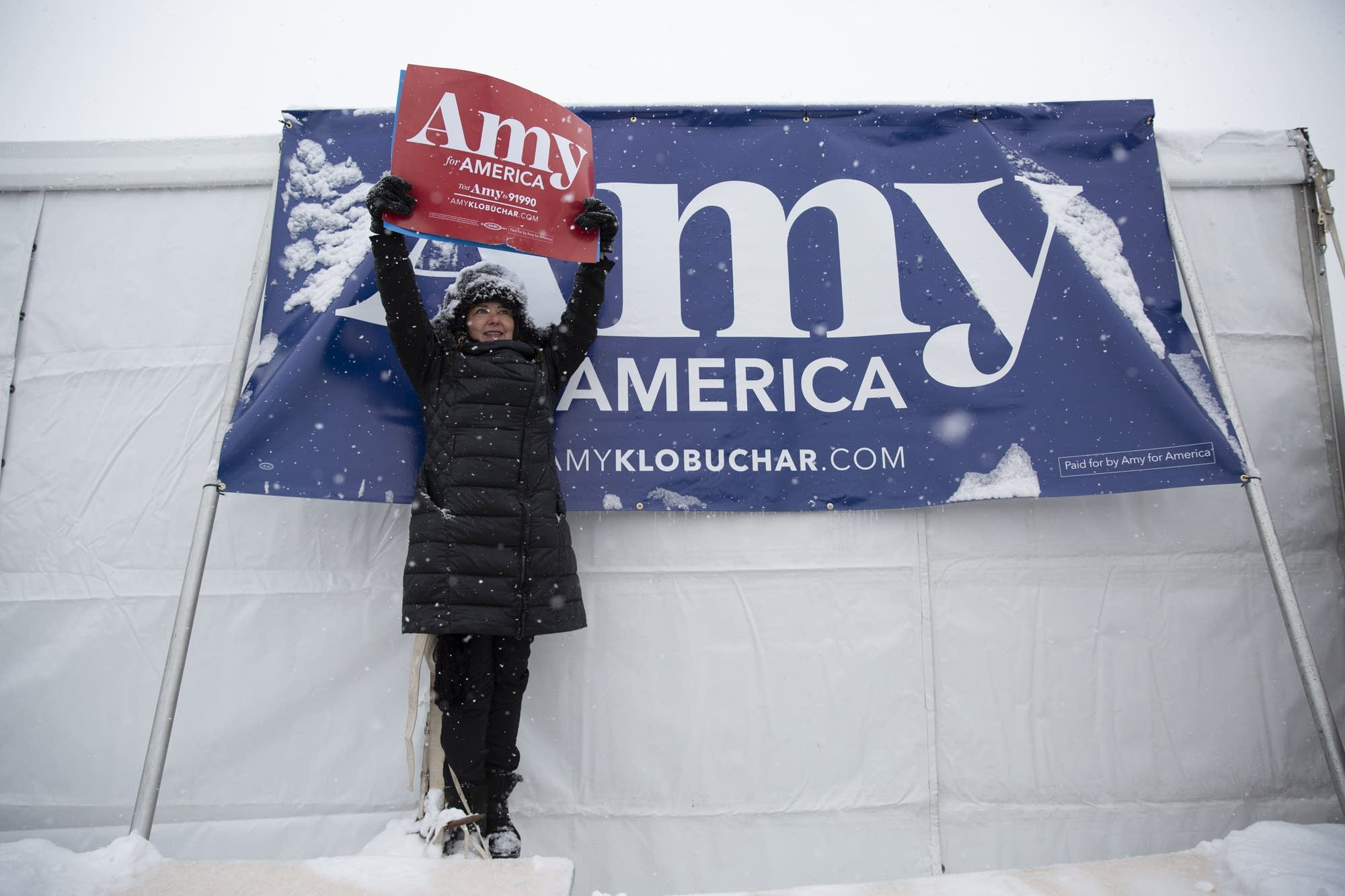 Jenifer Robins stands on a table to get a view during a rally.