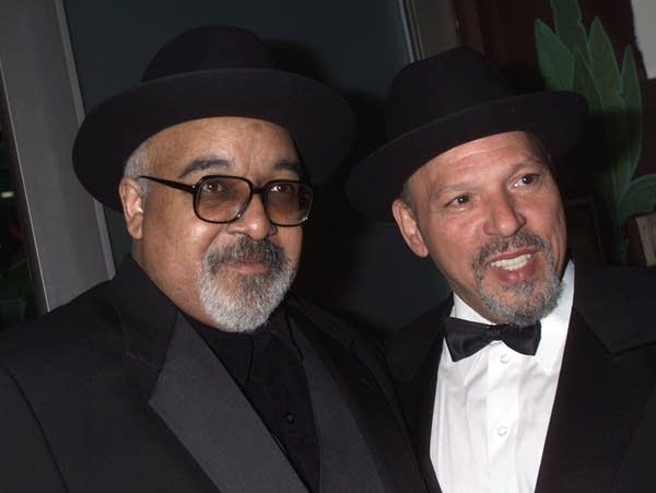 Two men dressed in suits and hats.