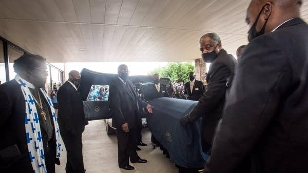Pallbearers move the casket of George Floyd