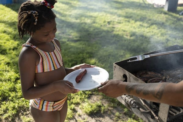 A dad hands his daughter a plate of grilled food.