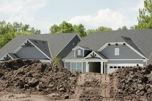 New homes peek out from behind mounds of excavated dirt.