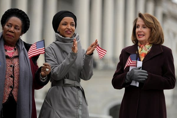 Rep. Ilhan Omar (D-MN), center, and House Speaker Nancy Pelosi at a rally.