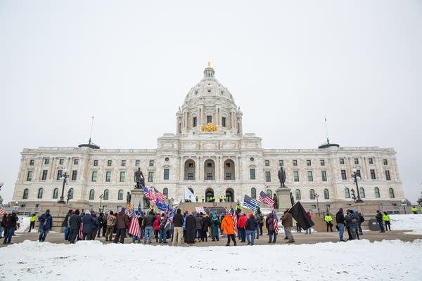 A group of people stand in front of the Capitol.