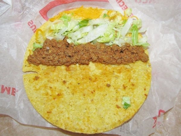 A taco bell taco pried open to show brown meat and lettuce