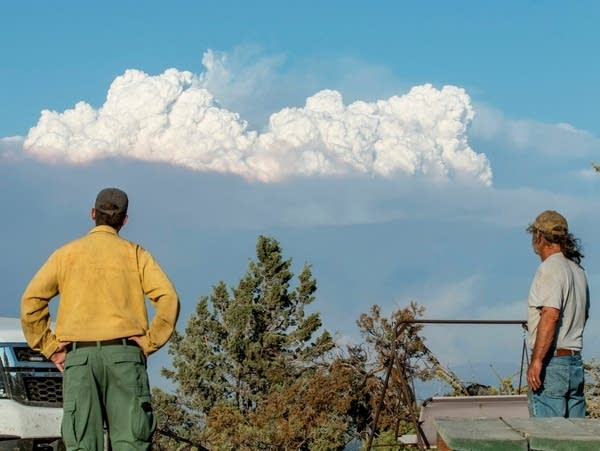 Two people watch a plume of smoke from a wildfire