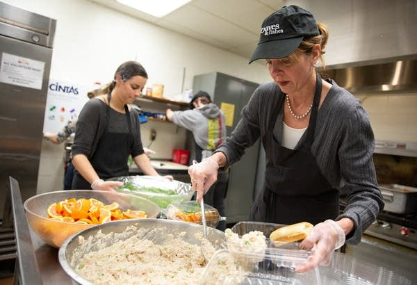 Loaves and Fishes executive director Cathy Maes helps prepare meals.