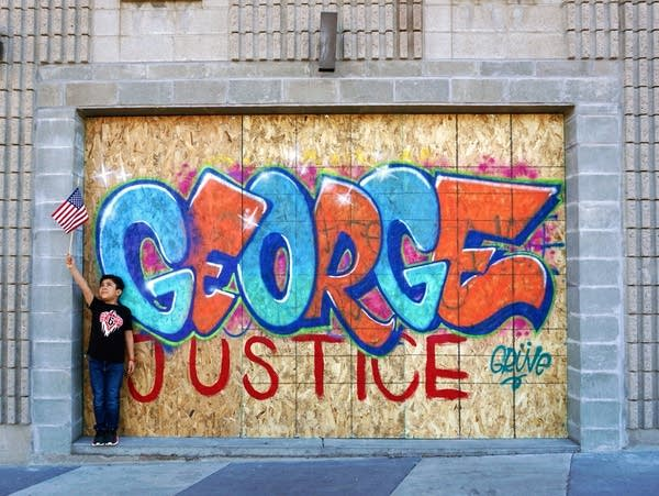 A boy holds an American flag in front of graffiti for George Floyd