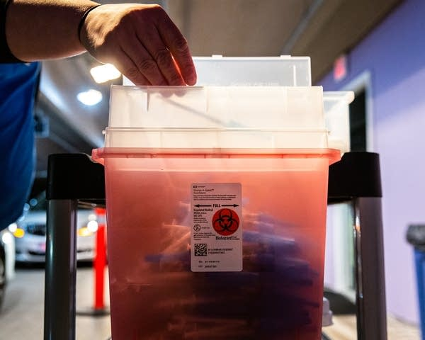 A syringe is dropped into a sharps container.
