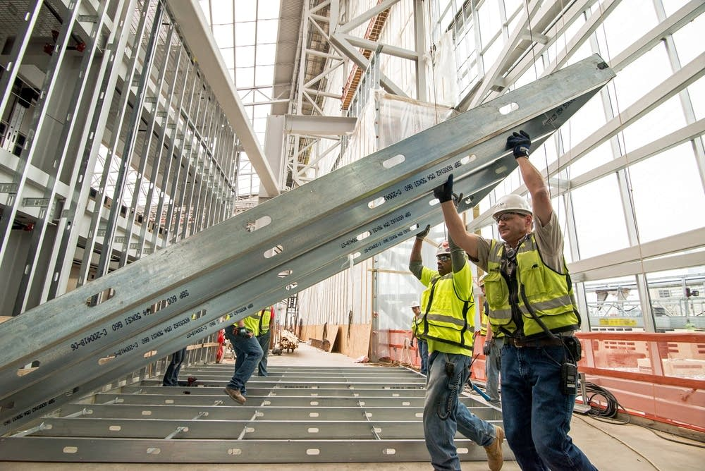 Construction workers move metal frames.