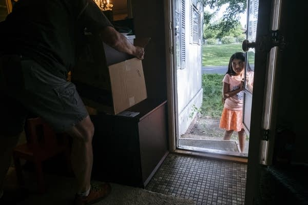 Eleven-year-old Ydira Sanchez holds the door of her mobile home.