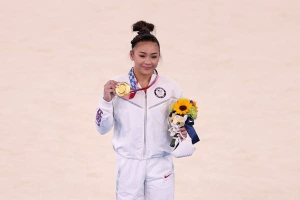 A woman poses with her Olympic gold medal.