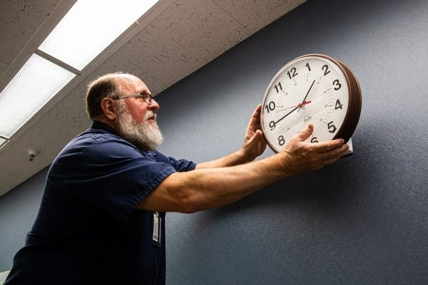 A man takes a clock off of a wall.
