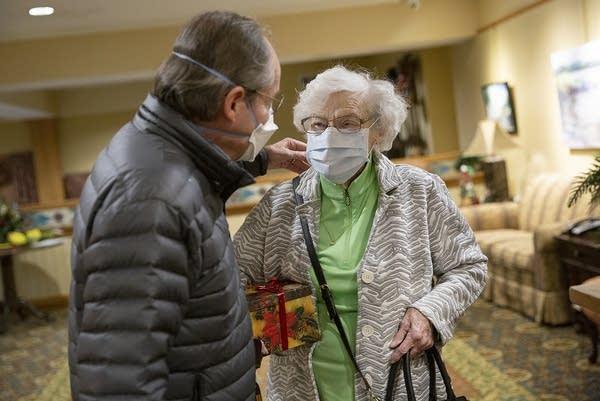 Two people wearing face masks hug.