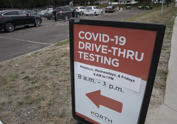 A sign provides information for COVID-19 testing site hours.
