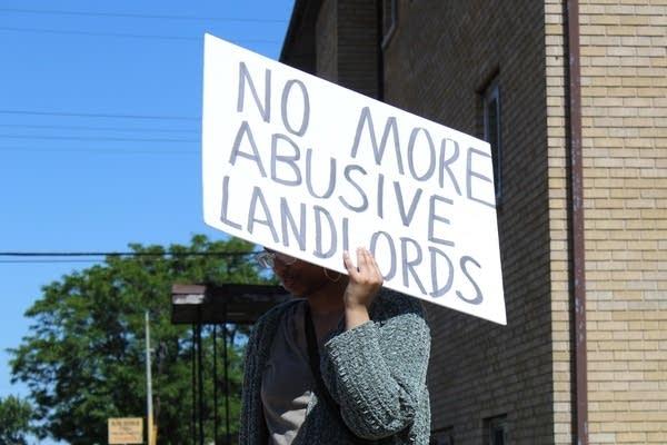 Kaaha Kaahiye holds a sign protesting gentrification.