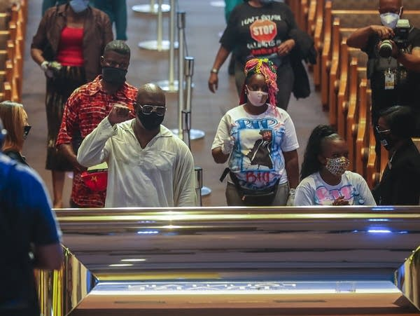 People gather next to a coffin during a visitation.