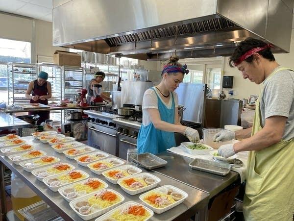 A kitchen staff work on meals.