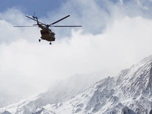 A rescue helicopter flies over the Dena mountains searching for wreckage.