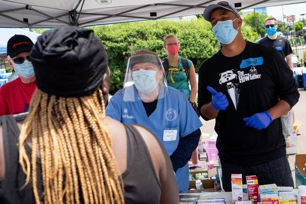 Two doctors pass out medical supplies during a resource giveaway.
