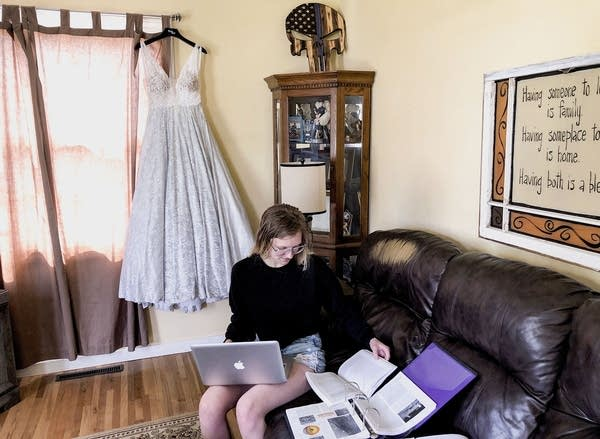 A teen sitting on a couch with a laptop surrounded by books.