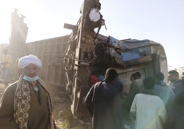 A group of people gather around a wrecked train carriage.
