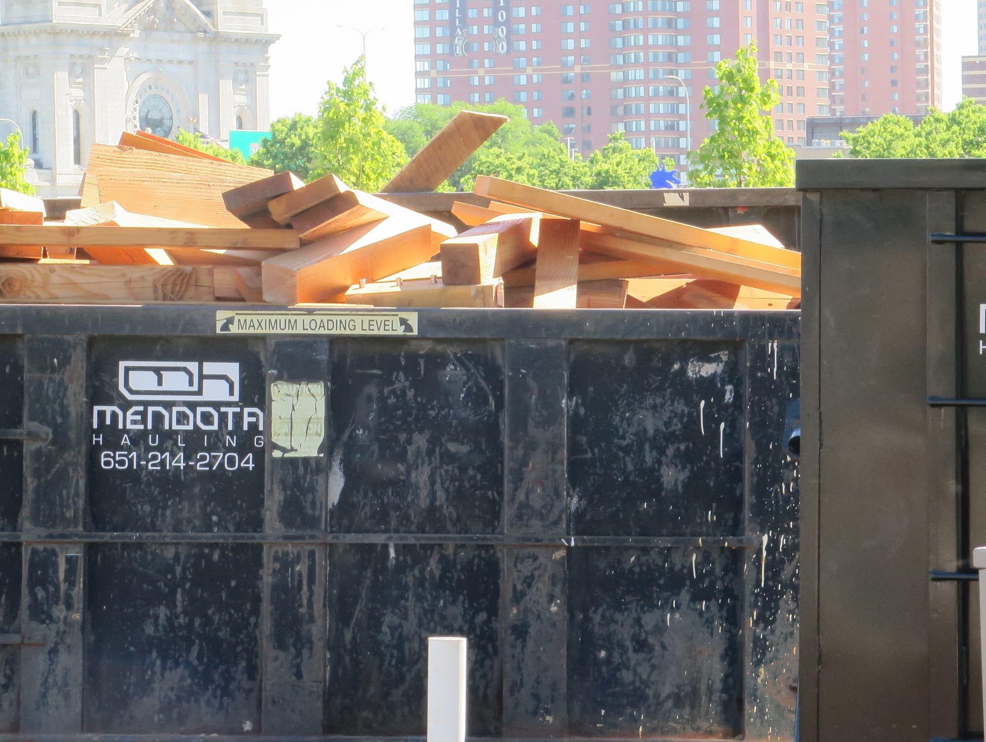 Workers cut up the wood and put it in construction dumpsters