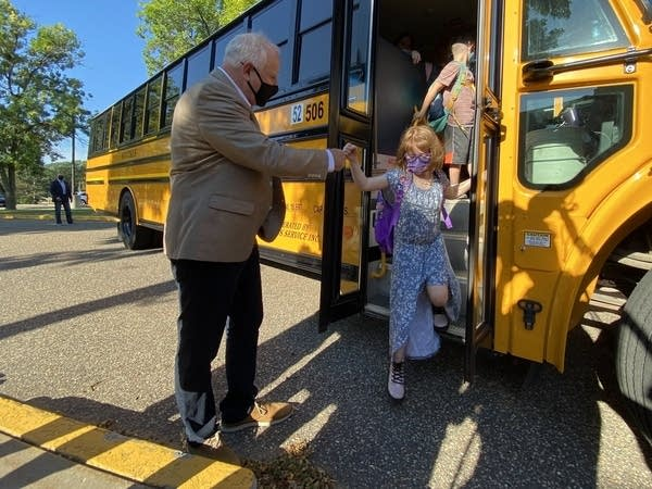 A man in a mask greets kids getting off a school bus.