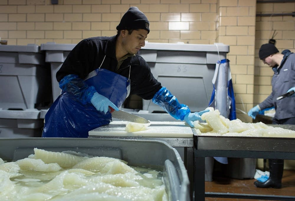 Pieces of lutefisk are cut and weighed