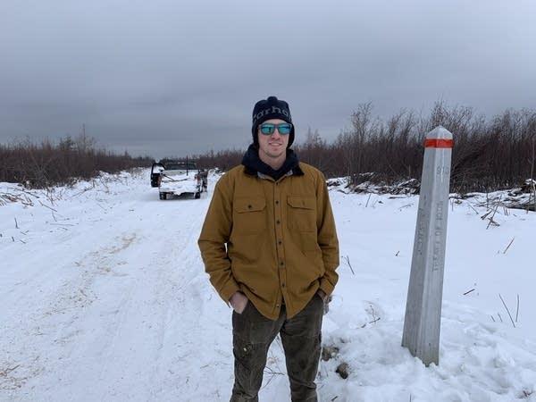 A man stands next to a metal pole