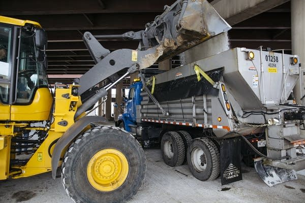 A snow plow truck is filled with road salt.