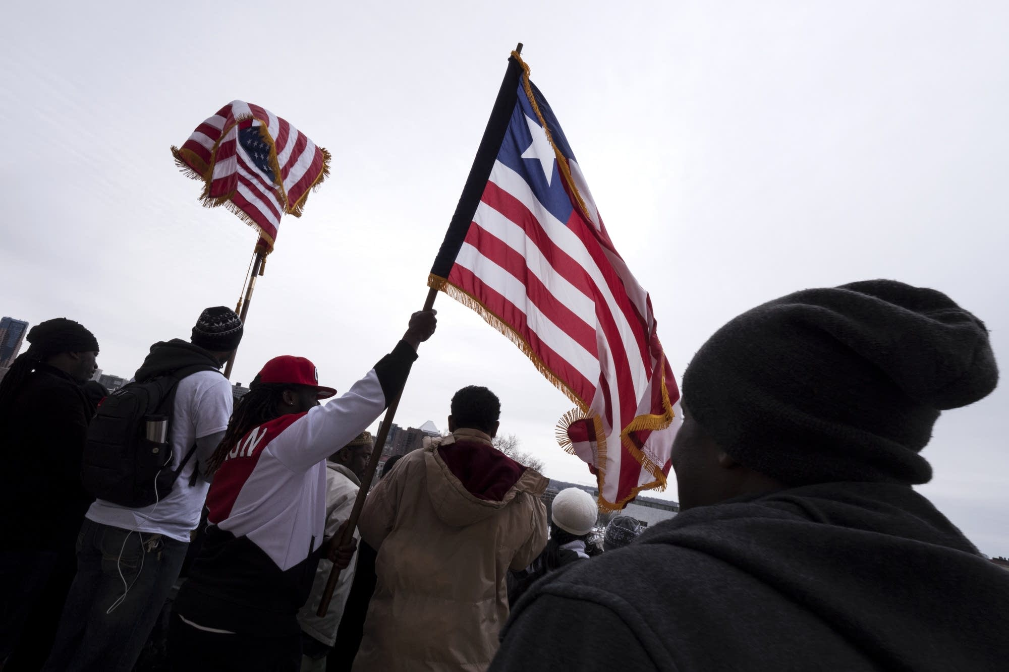 Flags of the U.S. and Liberia fly at the rally on the steps of the capitol.