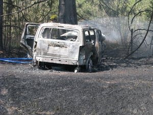 Firefighter sprays water on a burned vehicle